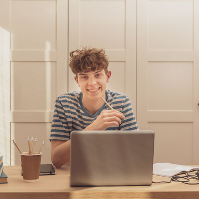 A nice teenage boy in headphones uses the laptop and learns at the desk in his room. He takes notes with a pencil. Distance learning because of the epidemic coronavirus